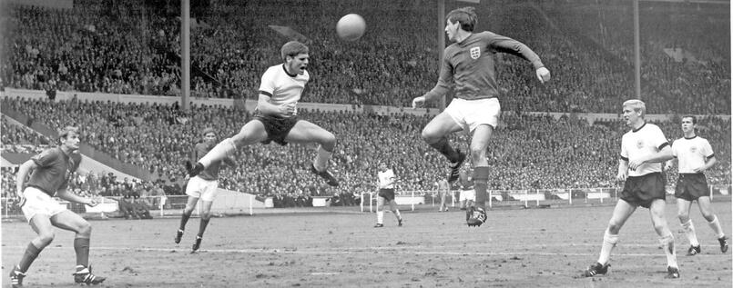 Martin Peters justs fails to get to a cross that is headed away by Wolfgang Weber.