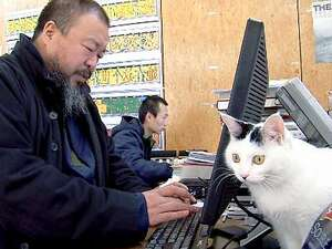 "The twitter-star Ai Weiwei sits in front of his computer with a cat, as seen in the film ""Ai Weiwei: Never Sorry."" ."