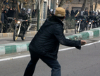 An Iranian protester throws a stone at riot police during fierce clashes in central Tehran