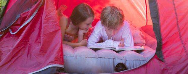 Boy and girl reading lying in a red tent with a book model released Symbolfoto PUBLICATIONxINxGERxSUIxAUTxHUNxONLY SARF001930