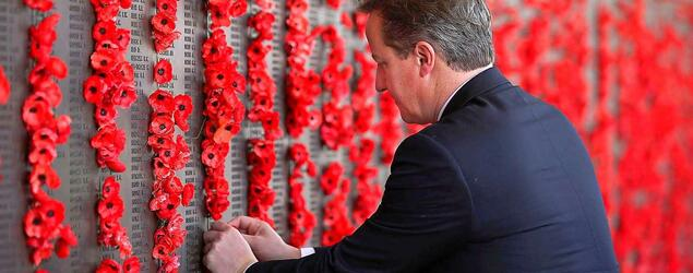 British Prime Minister David Cameron places a poppy along the Roll of Honour during a visit to the Australian War Memorial in Canberra.