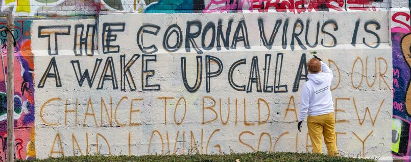 Im Münchner Schlachthofviertel schreibt ein Kunststudent ein Graffito auf eine Wand - mit dem Text: The corona virus is a wake up call and our chance to build a new and loving society.