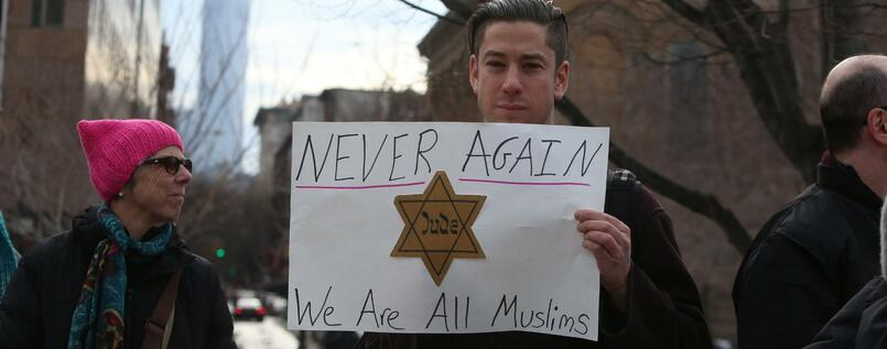 "Ein Demonstrant hält bei einem Protest im Washington Square Park in New York ein Plakat mit einem Judenstern und der Aufschrift ""Never again - We are all Muslims"". Die Demonstration richtete sich gegen US-Präsident Trumps Einreiseverbot, von dem Menschen aus sieben mehrheitlich islamisch geprägten Ländern betroffen waren."