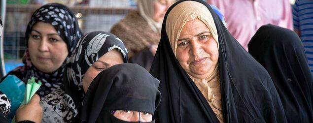 Iraqi women stand in line for relief. Every little space in the kurdish cities in Iraq are needed for refugees now.