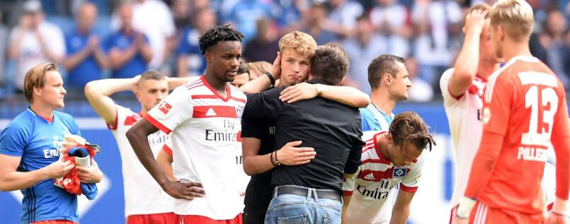 Hamburg's German head coach Christian Titz stands with the players on the pitch after the German first division Bundesliga football match Hamburger SV vs Borussia Moenchengladbach in Hamburg, northern Germany, on May 12, 2018. / AFP PHOTO / Patrik STOLLARZ / RESTRICTIONS: DURING MATCH TIME: DFL RULES TO LIMIT THE ONLINE USAGE TO 15 PICTURES PER MATCH AND FORBID IMAGE SEQUENCES TO SIMULATE VIDEO. == RESTRICTED TO EDITORIAL USE == FOR FURTHER QUERIES PLEASE CONTACT DFL DIRECTLY AT + 49 69 650050