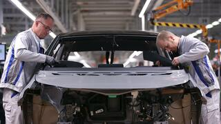 Two employees work on a production line of the new Volkswagen electric car, the ID.3 model, at the Volkswagen car factory in Zwickau, eastern Germany, on November 4, 2019.